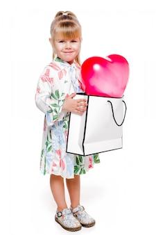 De imagem - menina, elegante, em, um, branco, floral, vestido, segura, um, grande, sacola, com, um, coração amoldado, balão, dentro.