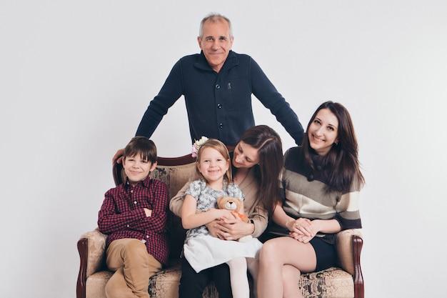 De infância feliz, família, amor, grupo de pessoas em um branco, adultos e crianças com brinquedos, sentado no mesmo sofá