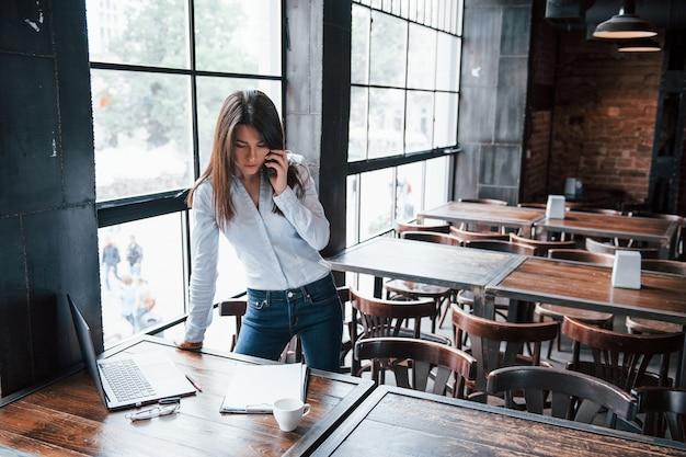 De jeans. mulher de negócios com roupas oficiais está dentro de casa no café durante o dia.