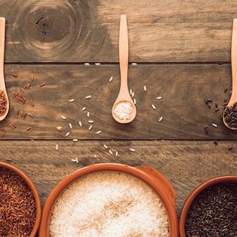 De madeira e tigelas com grãos de arroz orgânico na mesa de madeira