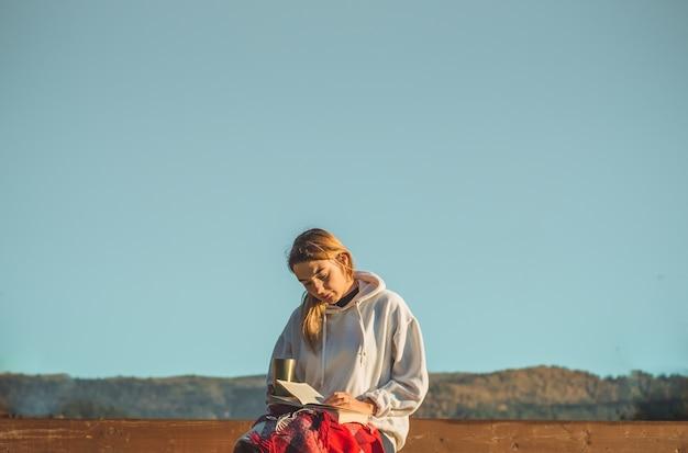 De manhã, a garota se senta em um banco de madeira nas montanhas na natureza, lê um livro e bebe chá quente em uma xícara térmica. conceitos de leitura na natureza. treinamento ao ar livre