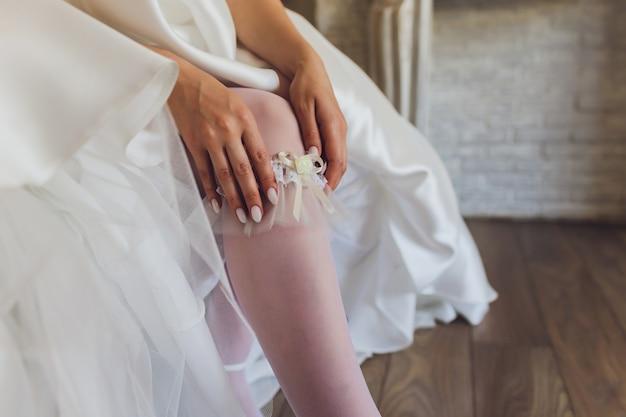 De manhã, a noiva de meias e um vestido de noiva branco usa uma liga na perna, a noiva está segurando as mãos para a liga.