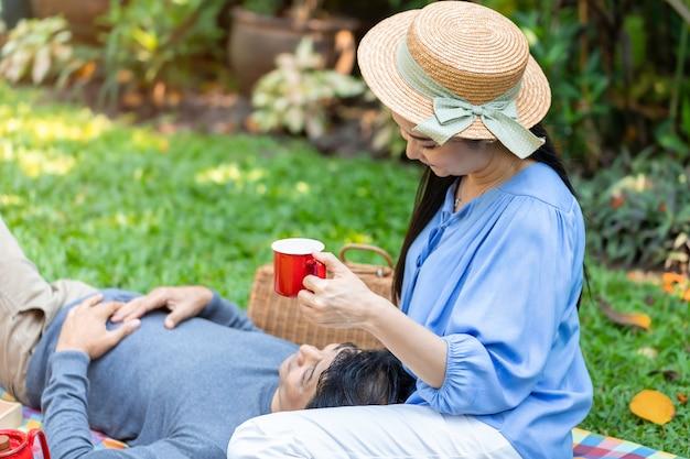 De manhã. casal asiático sênior, bebendo café e piquenique no parque.