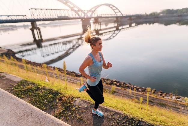 De manhã cedo correndo. loiro bonito apto garota correndo pelo rio