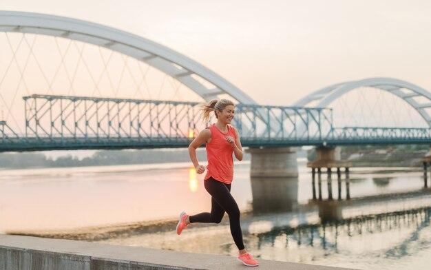 De manhã cedo correndo. menina loura bonita do ajuste que corre pelo rio antes do trabalho.