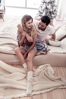 De manhã cedo. mulher loira e bonita de cabelos compridos vestindo shorts sentada na cama com seu marido moreno