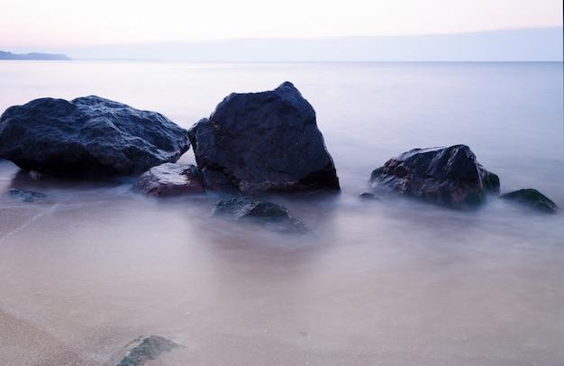 De manhã cedo na costa rochosa do mar. água suave do mar por causa da longa exposição. tempo de nascer do sol.