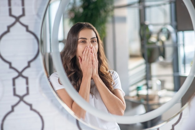 De manhã cedo. uma jovem sonolenta bocejando perto do espelho