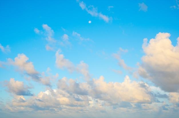 De manhã, o fundo do céu azul com a lua e pequenas nuvens.