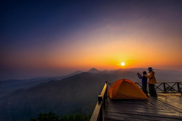 De manhã. os turistas assistem o nascer do sol em um balcão de madeira.
