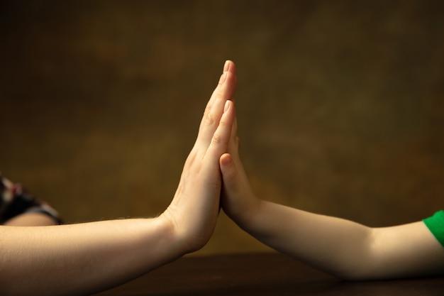 De mãos dadas, batendo palmas como amigos. close-up tiro das mãos femininas e infantis fazendo coisas diferentes juntos. família, casa, educação, infância, conceito de caridade. mãe e filho ou filha, riqueza.