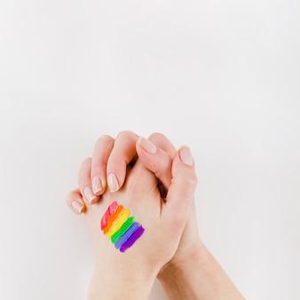 De mãos dadas com uma bandeira do orgulho pintado