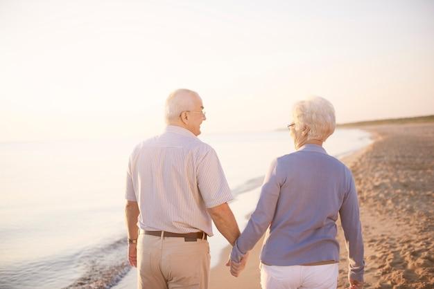 De mãos dadas enquanto caminha pela praia
