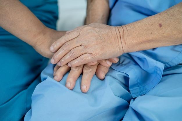 De mãos dadas, paciente asiática idosa ou idosa com amor, cuidado, incentivo e empatia na enfermagem