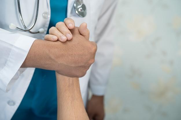 De mãos dadas, paciente asiático sênior ou idosa com amor, cuidado, incentivo e empatia na enfermaria do hospital de enfermagem, conceito médico forte e saudável