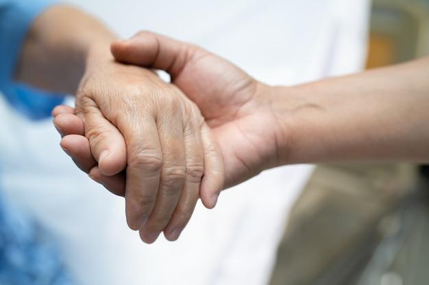 De mãos dadas, paciente idoso asiático ou idosa com amor, cuidado, incentivo e empatia na enfermaria do hospital de enfermagem, conceito médico forte e saudável
