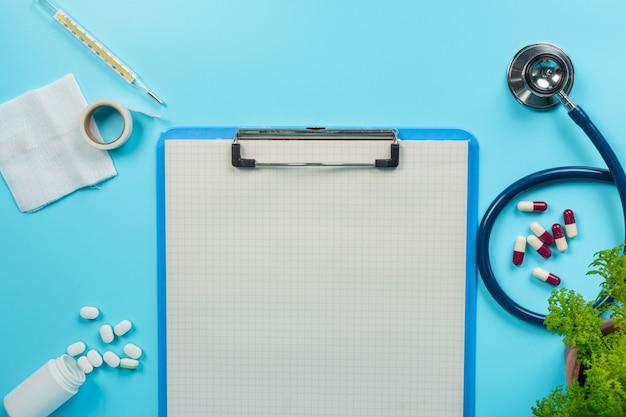 De medicamentos, suprimentos médicos colocados ao lado de pranchetas e ferramentas médicas em um azul.