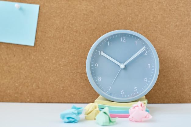 De notas, objetivos, memorando ou plano de ação. notas auto-adesivas em uma placa de cortiça e despertador no escritório ou em casa