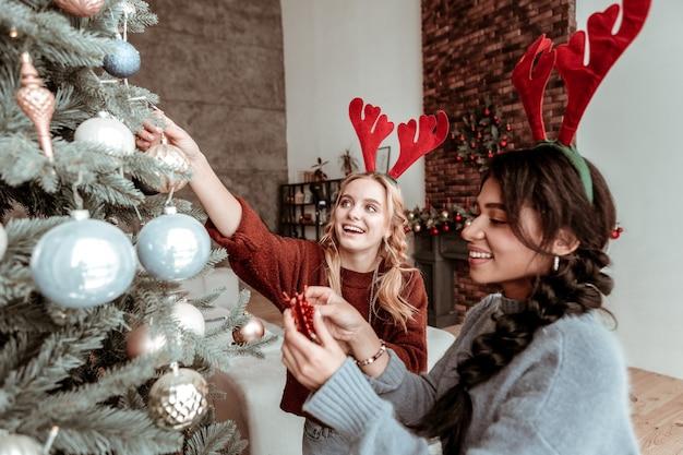 De ótimo humor. garotas de cabelos compridos sorridentes ocupadas decorando uma árvore de natal e usando orelhas de veado