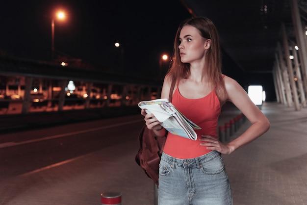 De pé à noite com o mapa nas mãos e esperando o táxi Foto Premium