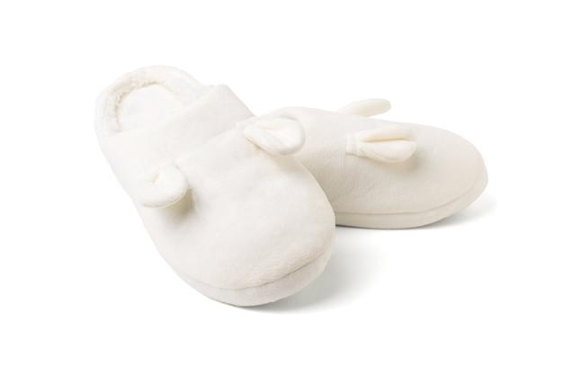 De pé em cima uns dos outros, chinelos de casa brancos isolados em um fundo branco. sapatos confortáveis para casa.
