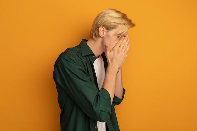 De pé em vista de perfil com olhos fechados, jovem loiro vestindo uma camiseta verde e cobrindo o rosto com as mãos