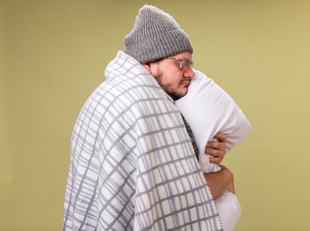 De pé em vista de perfil com os olhos fechados, homem doente de meia-idade usando chapéu de inverno e lenço enrolado em um travesseiro xadrez abraçado