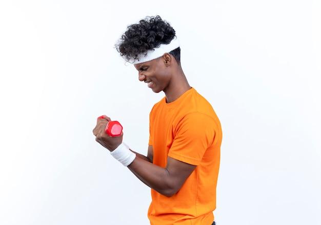 De pé em vista de perfil, jovem afro-americano, tenso e esportivo, usando fita para a cabeça e pulseira, fazendo exercícios com halteres