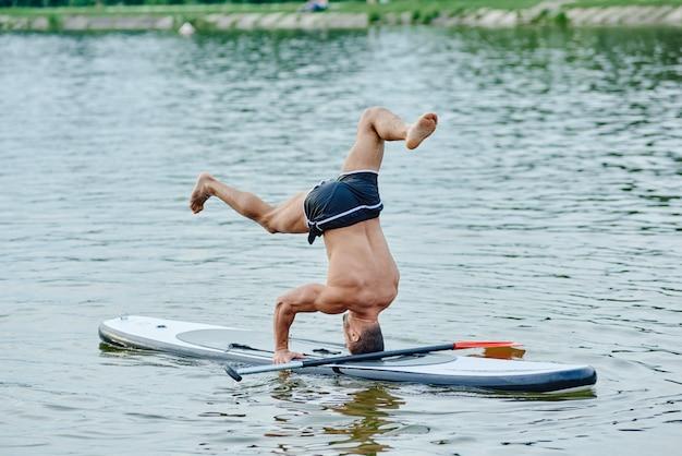De pé na cabeça, fazendo exercícios de ioga, nadando em sup boad no lago da cidade.