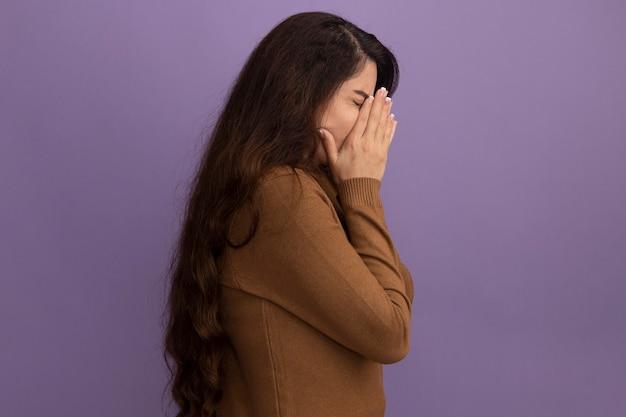 De pé na vista de perfil, com os olhos fechados, bela jovem vestindo um suéter de gola alta marrom coberto com as mãos isoladas na parede roxa