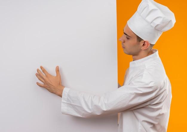 De pé na vista de perfil, jovem homem descolado vestindo uniforme de chef segurando uma parede branca com espaço de cópia