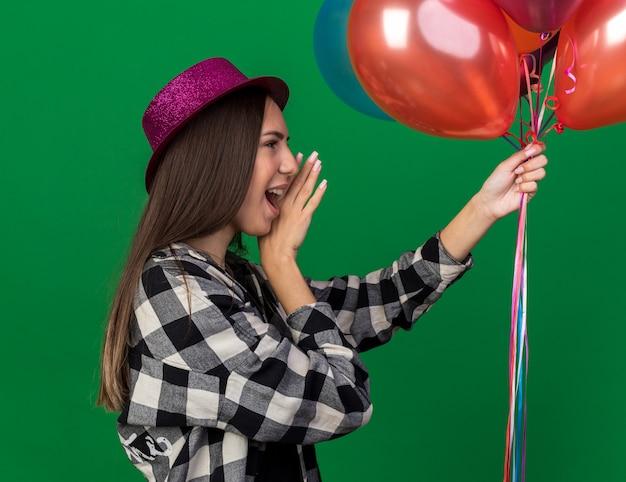 De pé na vista de perfil, jovem linda com chapéu de festa segurando balões