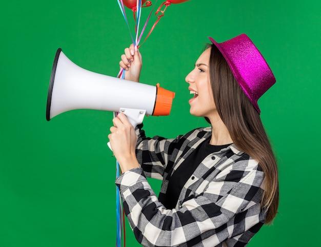 De pé na vista de perfil, uma jovem linda com um chapéu de festa segurando balões e falando no alto-falante