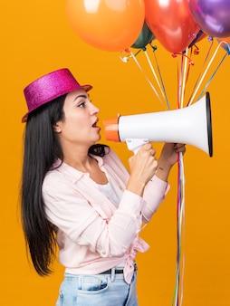 De pé na vista de perfil, uma jovem linda usando um chapéu de festa segurando balões fala no alto-falante isolado na parede laranja