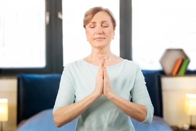 De pé no quarto. mulher adulta tranquila em estado meditativo enquanto faz uma sessão de ioga em seu quarto claro