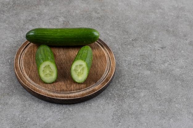 De pepinos saudáveis cortados inteiros ou pela metade na placa de madeira.