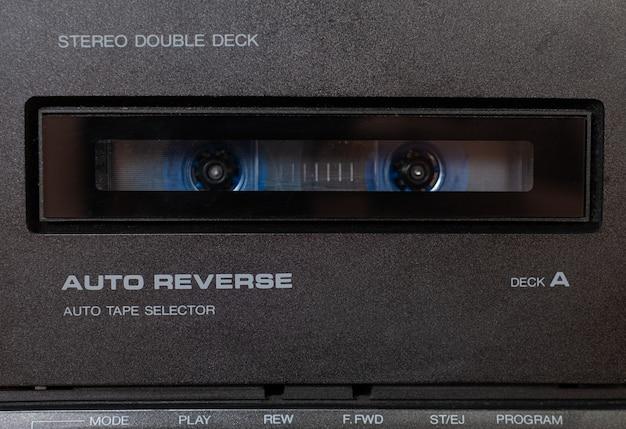 De perto, um gravador de um toca-fitas estéreo vintage com tecnologia retro