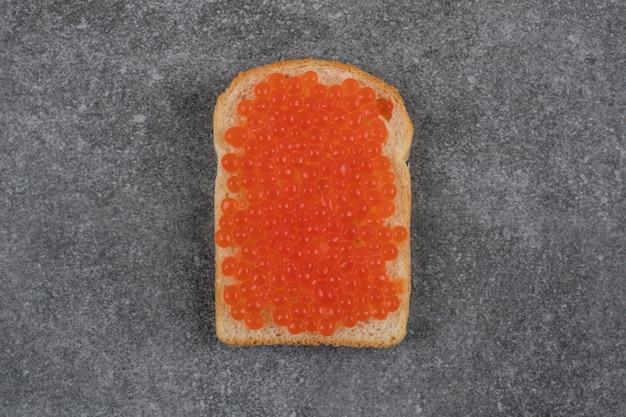 De sanduíche fresco com caviar vermelho na mesa cinza.