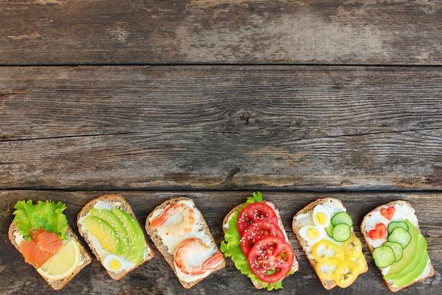 De sanduíches diferentes no fundo de madeira velho. vista do topo. lay plana.