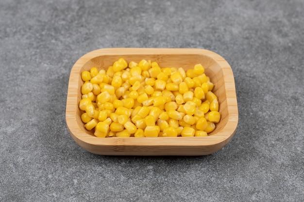 De sementes de milho doce em conserva em uma tigela de madeira.