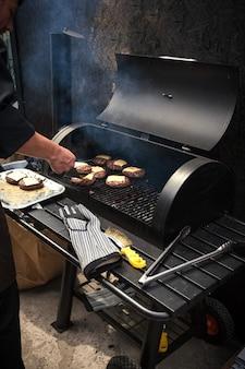 De um homem cozinhando carne marmorizada em um churrasco para hambúrgueres