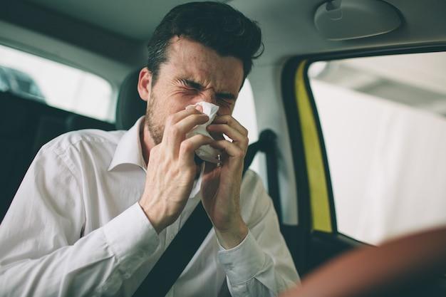 De um jovem com lenço. cara doente tem corrimento nasal. homem faz uma cura para o resfriado comum no carro