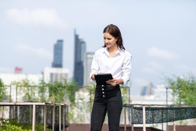 De uma jardineira trabalhando na horta no telhado de um edifício moderno Foto Premium