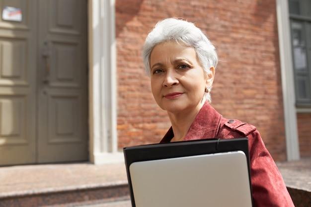 De uma mulher moderna ocupada de meia-idade com cabelos grisalhos posando do lado de fora de um prédio de tijolos, carregando um estiloso gadget digital para trabalho remoto ou educação online