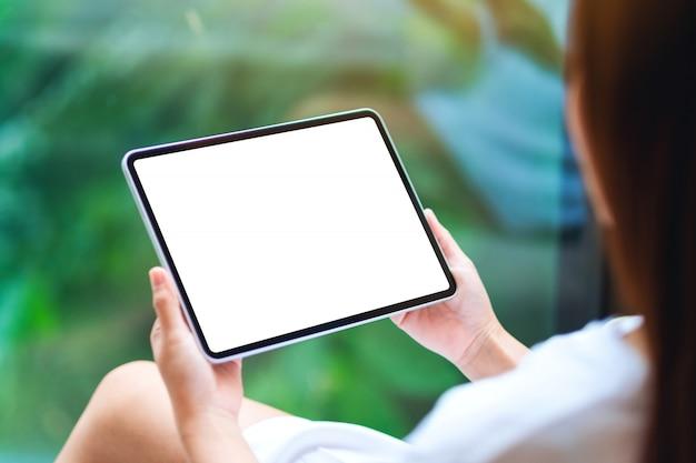 De uma mulher segurando preto tablet pc com tela branca de mesa em branco, natureza verde