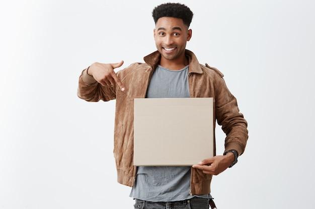 Dê uma olhada neste. feche o retrato do jovem estudante universitário masculino de pele negra linda com penteado afro em roupas de outono elegantes, apontando para a placa da caixa nas mãos com expressão feliz