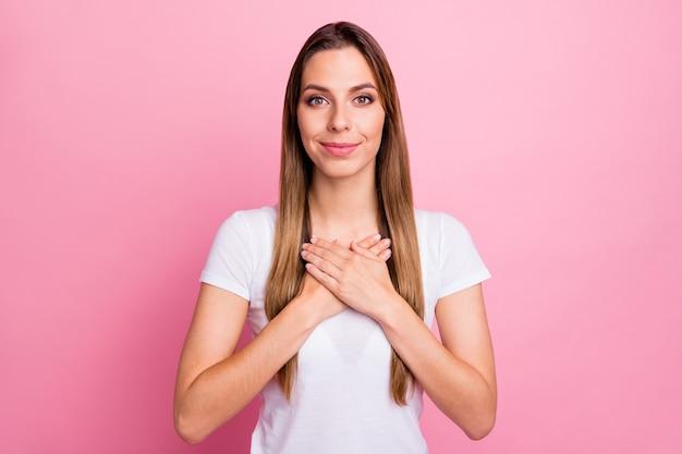 De uma senhora bonita e pacífica, com as palmas das mãos no peito, expressando as melhores emoções cardíacas, use uma camiseta branca casual
