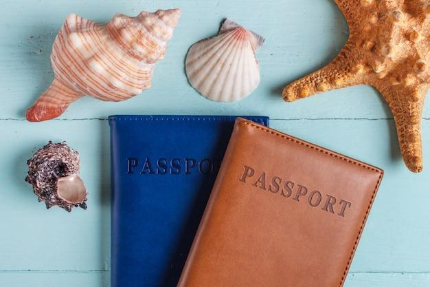 De viajar, férias, cruzeiro marítimo. passaportes, conchas do mar em um fundo de madeira. período de férias.