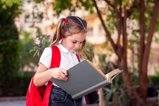 De volta à escola. aluno lendo livro ao ar livre