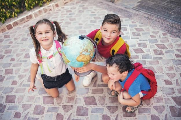 De volta à escola. alunos com globo ao ar livre. geografia e conceito de educação